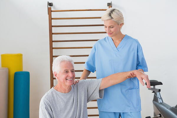 Senior man stretching with his therapist in fitness studio-1