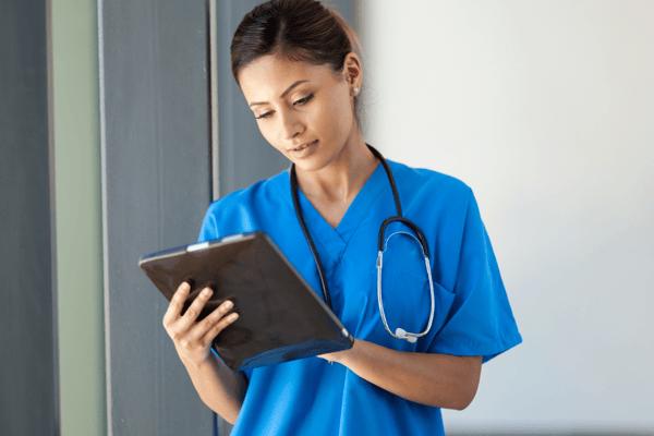 nurse writing on tablet