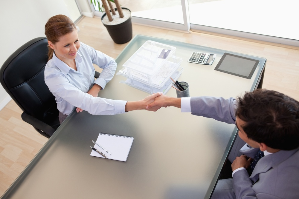 Above view of young consultant shaking hands with her client.jpeg