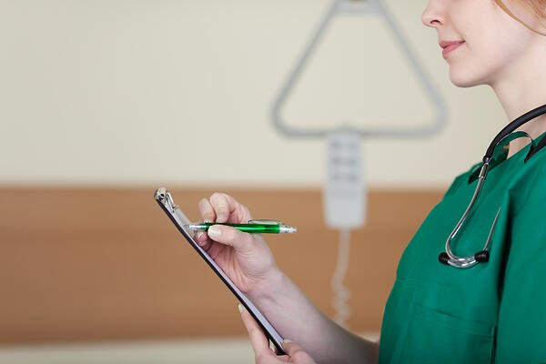 Close up of the profile of a young female doctor or nurse taking patient notes on the ward-1