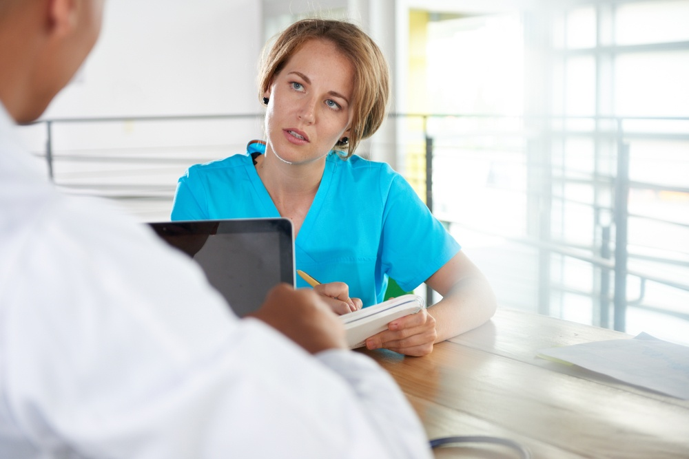 Team of doctor and nurse discussing a patient diagnosis sitting at the desk in bright modern office.jpeg