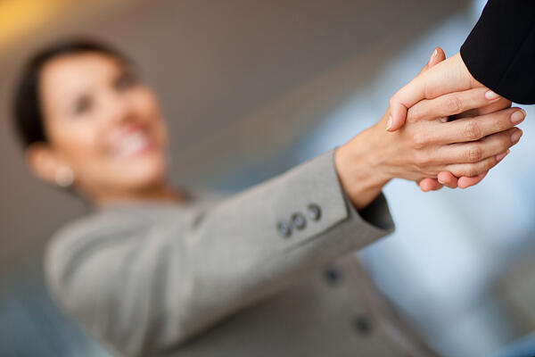 Welcoming business woman giving a handshake and smiling-1
